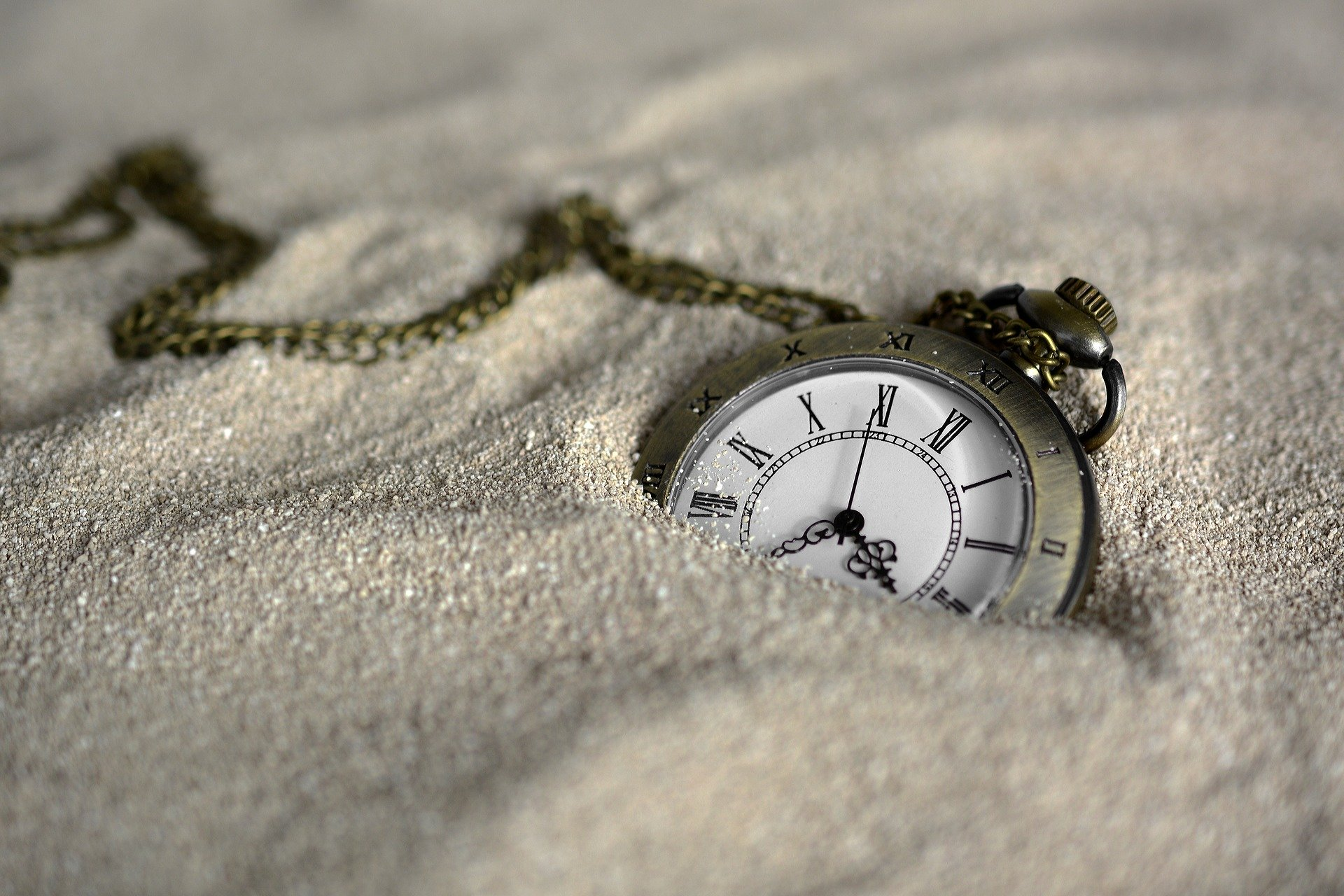 Pocket watch sinks into the sand